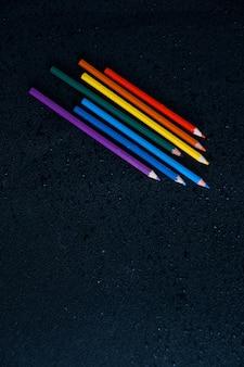 Regenbogenfarbstifte auf einem nassen schwarzen hintergründigen lgbt-symbolkopierraum lassen wasser fallen