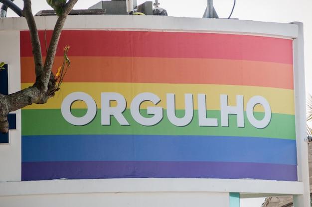 Regenbogenflagge mit dem wort stolz geschrieben auf portugiesisch am strand der copacabana in rio de janeiro brasilien.