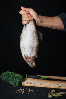 Regenbogenforelle in den händen eines männlichen chefs auf küche. frischer roher fisch