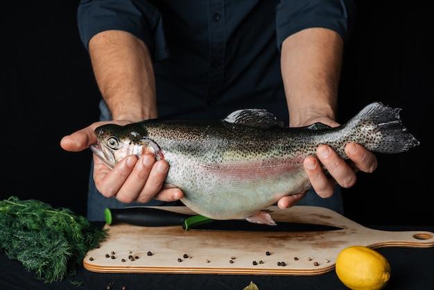 Regenbogenforelle in den händen eines männlichen chefs im hintergrund der küche. frischer roher fisch