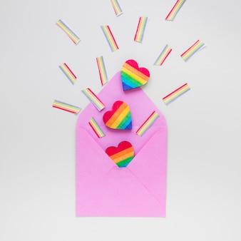 Regenbogenherz mit papierregenbogen zerstreut vom umschlag