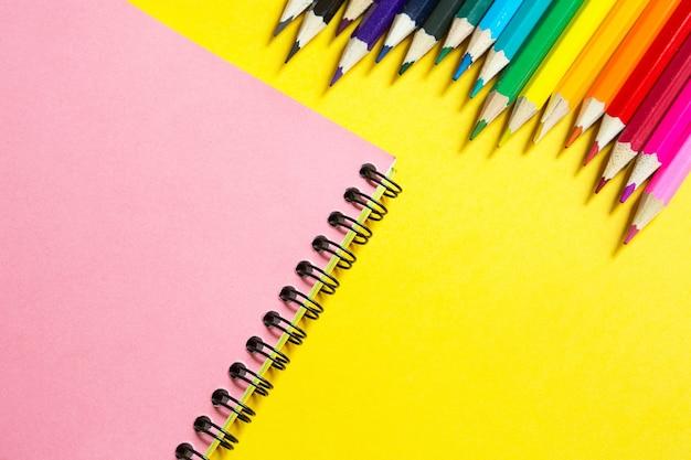 Regenbogenpalette von buntstiften mit einem spiralblock auf gelbem grund