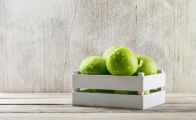 Regengrüne äpfel in einer holzkiste auf schmutz und hellem hölzernem hintergrund.