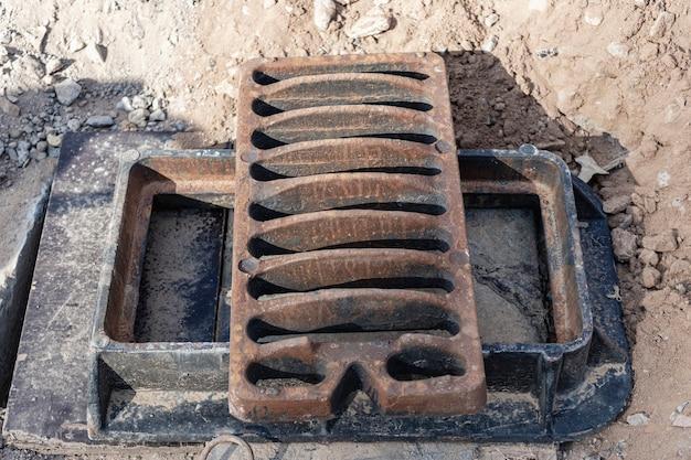 Regenkanal-straßenluke bereit für die installation. nahaufnahme. straßenarbeiten. sammlung und entsorgung von regenwasser von der straße.