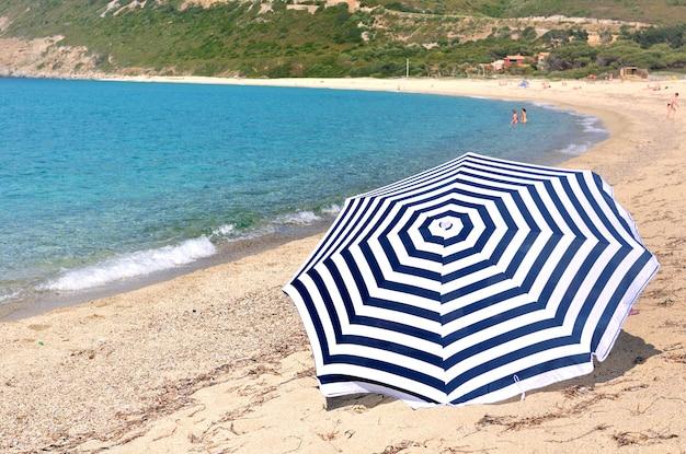 Regenschirm am strand von korsika mit türkisfarbenem meer