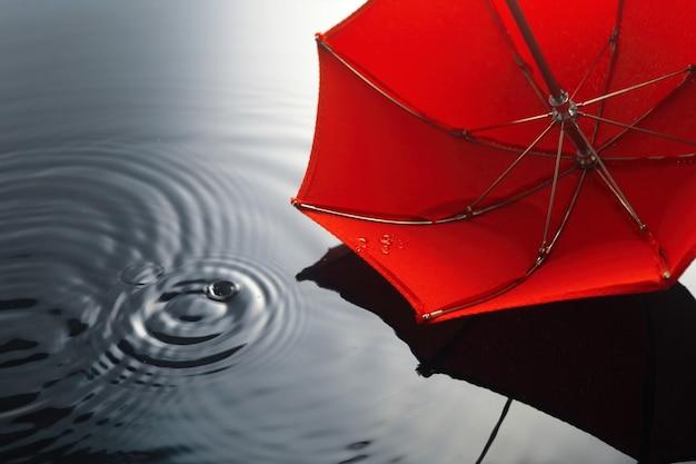 Regenschirm im regen. regenschirm in pfütze. herbst hintergrundkonzept.