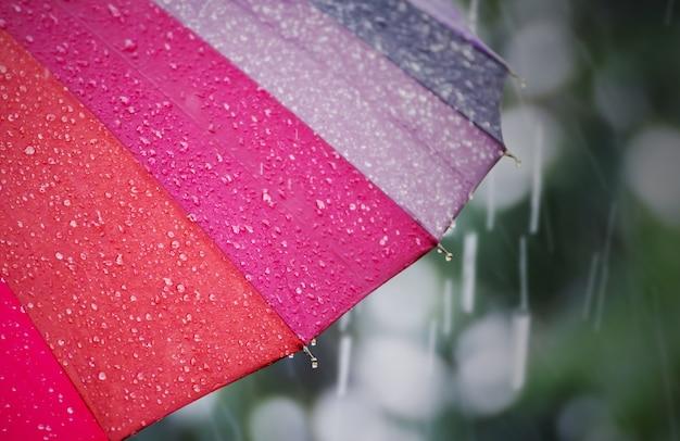 Regenschirm mit regentropfen am regnerischen tag