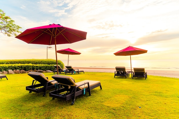 Regenschirm mit stuhl mit strandhintergrund und sonnenaufgang am morgen - ferien- und ferienkonzept