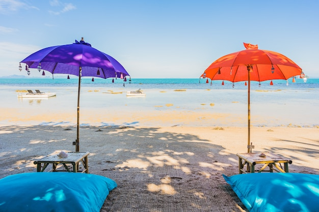 Regenschirm um schönen strandmeerozean für feiertagsferienreise