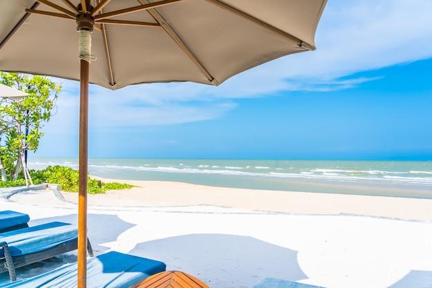 Regenschirm und stuhl auf dem strandseeozean mit blauem himmel und weißer wolke