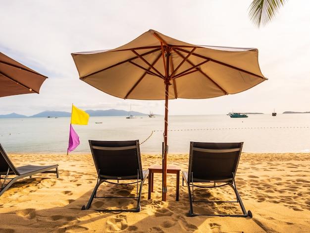 Regenschirm und stuhl auf dem tropischen strandmeer und -ozean zur sonnenaufgangzeit