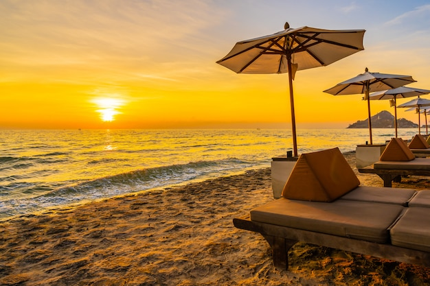Regenschirm und stuhl mit kissen um schöne landschaft von strand und meer