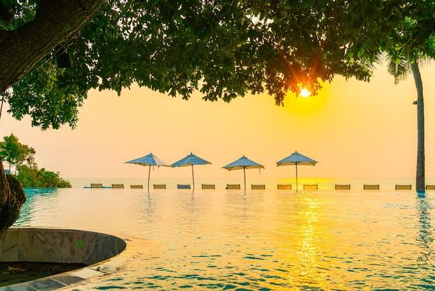Regenschirm und stuhl um schwimmbad mit meerblick für urlaubsreisekonzept