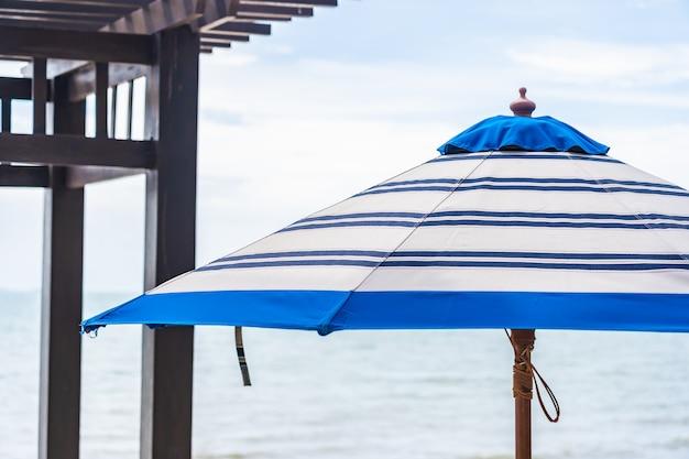 Regenschirm und stuhl um strandmeer mit blauem himmel