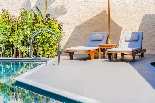 Regenschirm und stuhl um swimmingpool neary seeozean setzen mit blauem himmel und weißer wolke auf den strand