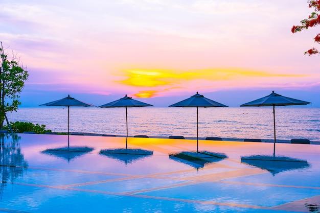 Regenschirm und stuhl um swimmingpool neary seeozean setzen zur sonnenaufgangs- oder sonnenuntergangzeit auf den strand