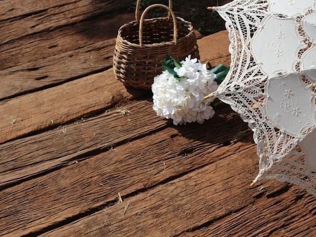 Regenschirm, weißer gefälschter hortensienblumenstrauß und weidenrattankorb auf holzboden