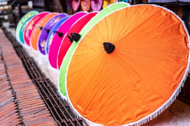 Regenschirme aus bunten stoffen auf seitlichem fußweg, thailändisches kunsthandwerk.