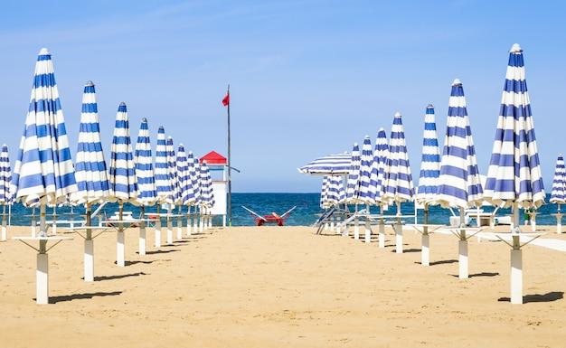 Regenschirme und rettungsstation am strand von rimini - italienischer sommer