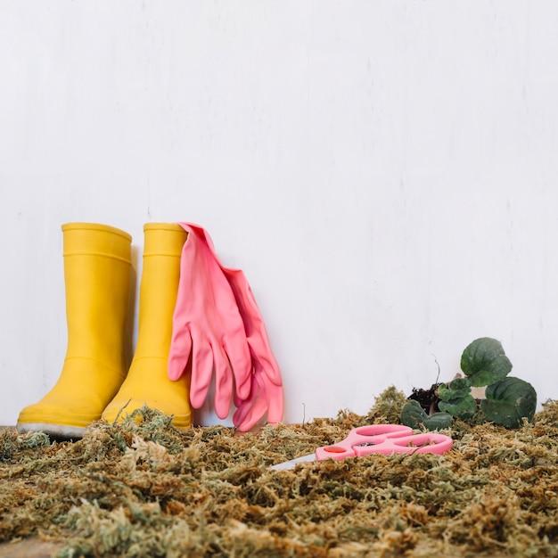 Regenstiefel und gummihandschuhe auf moos