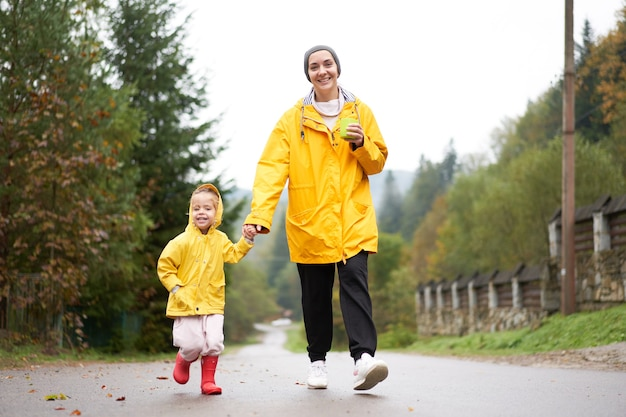 Regentag mutter und kleine tochter, die nach regen gehen, zogen gelben regenmantel an