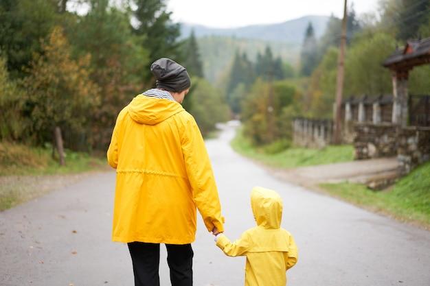 Regentag mutter und kleine tochter gehen nach dem regen gekleideten gelben regenmantel glückliche familie mit einem kind