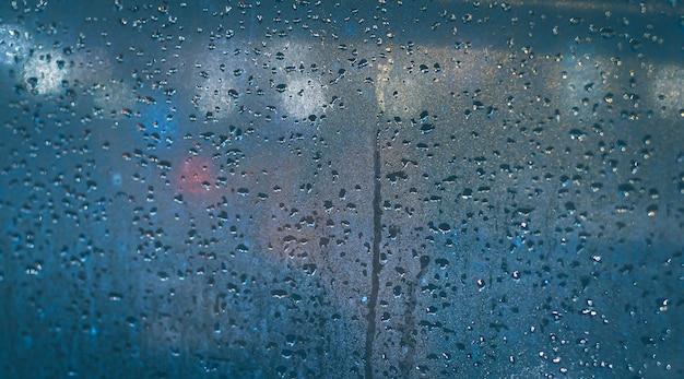 Regentropfen am fenster des autos. abstraktes unschärfebokeh des verkehrs und der autolampe.