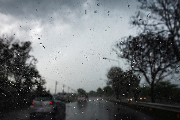 Regentropfen auf dem autoglas während der fahrt durch starken regen und sturmfluten.