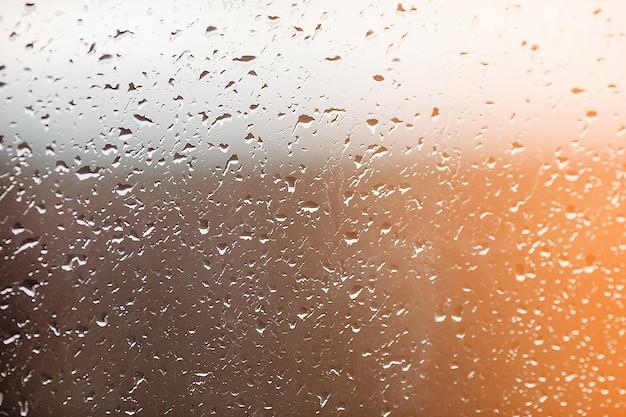 Regentropfen auf dem fenster. wasser auf dem glas. laufende tropfen. hintergrund konzeptionell.