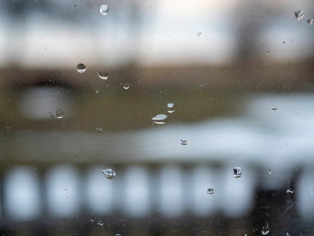 Regentropfen auf dem schmutzigen glas. im hintergrund eine verschwommene ländliche landschaft