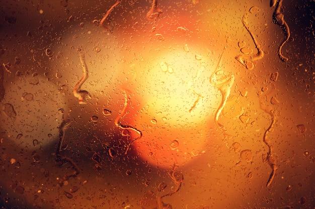 Regentropfen auf einem autofenster mit schön verschwommenem hintergrund der straßenampeln
