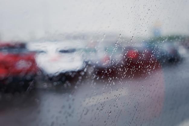 Regentropfen auf einem fenster und einer straße mit autos im hintergrund