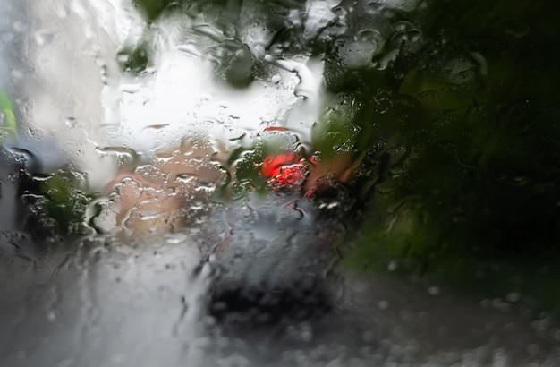 Regentropfen auf einer windschutzscheibe mit verschwommenen nachtlichtern der stadt im hintergrund.