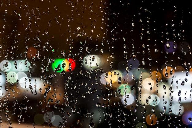 Regentropfen auf fenster, nacht, nahaufnahmehintergrund