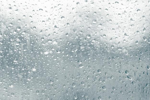 Regentropfen auf glas auf dem hintergrund von moskitonetzen im herbst nasse regenzeit