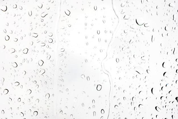 Regentropfen auf glas. silhouetten von wassertropfen auf einer transparenten oberfläche.