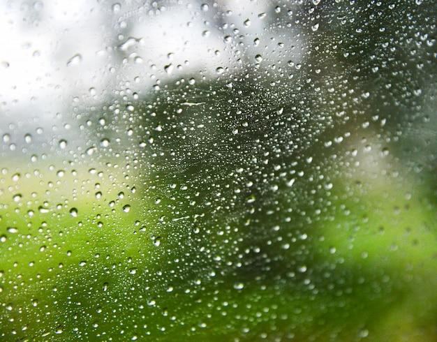 Regentropfen auf regnerischen glasfenster mit regen lässt naturhintergrund fallen