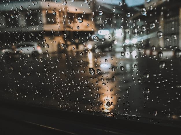 Regentropfen, die nachts am glas haften, vermitteln ein gefühl der einsamkeit.