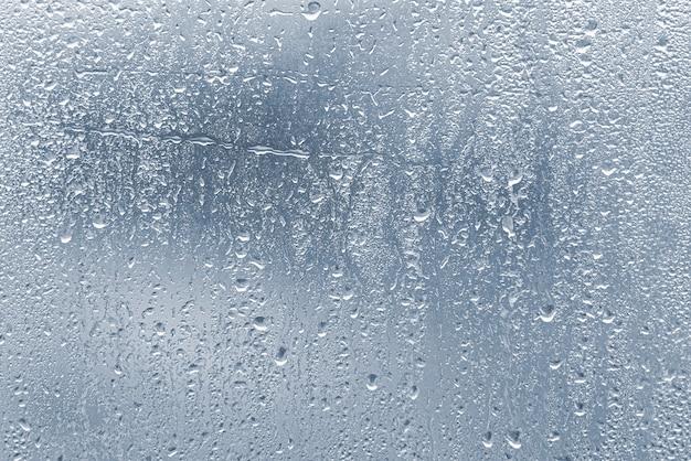 Regentropfen, kondenswasser am glasfenster bei starkem regen, wassertropfen auf blauem glas