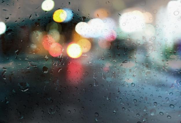 Regentropfen mit hellem bokeh auf dem straßenregen-saisonhintergrund