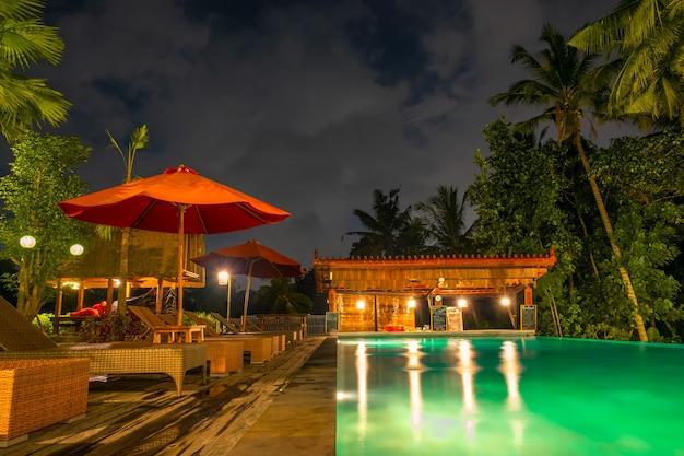 Regenwald mit palmen. pool ohne personen mit hintergrundbeleuchtung wasser. sonnenliegen und sonnenschirme. nacht. die bar ist geschlossen