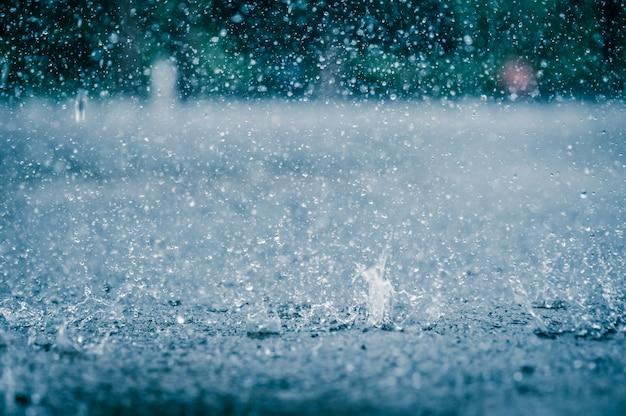 Regenwassertropfen, der an starkem regentag auf den straßenboden der stadt fällt