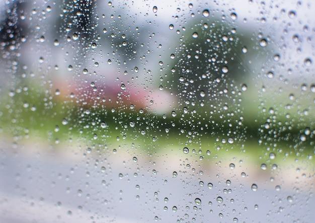 Regenwassertropfen und -text auf fenster mit abstraktem unschärfehintergrund