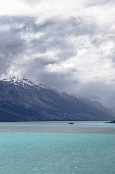 Regenwolken über den schneekappen der berge wakatipu see neuseeland