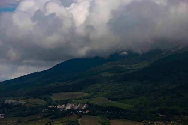 Regenwolken über der bergkette und dem meer. landschaft