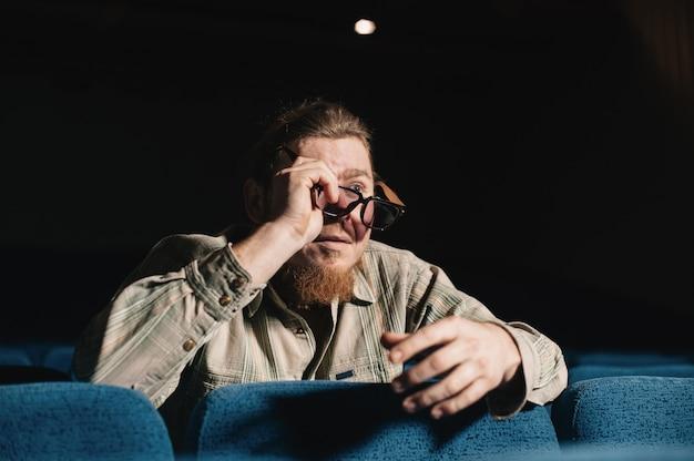 Regisseur nach dem anderen im dunklen theatersaal. porträt des kreativen mannes im zurückhaltenden. alleine kunstperson im konzertsaal. überraschter kritiker bei premiere. glücklicher brutaler bärtiger mann mit brille im kulturhaus.