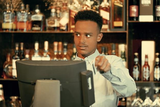 Registrierung männlich des barkeeper-mitarbeiters einer neuen bestellung durch eine registrierkasse.