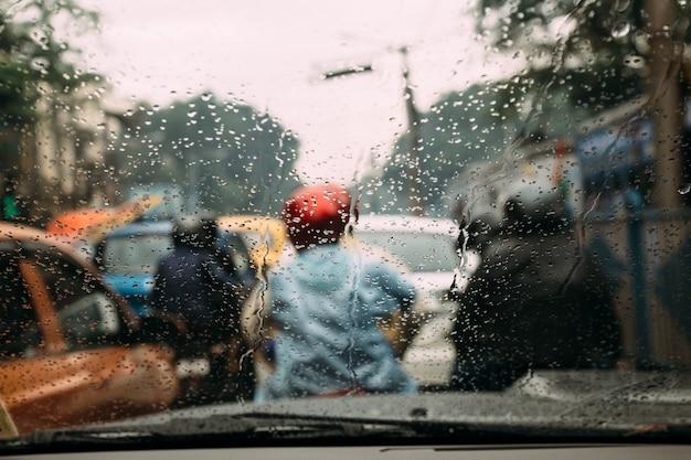 Regnen sie tropfen auf autoglas mit unschärfeverkehrsstau in kolkata, indien.
