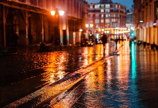 Regnerische nacht in einer großen stadt, reflexionen von lichtern auf der nassen straßenoberfläche.