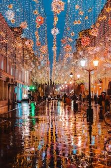 Regnerische nacht in einer großstadt, die reflexion der bunten stadt beleuchtet auf der nassen straßenoberfläche. ansicht einer fußgängerzone mit heller stadtfeiertagsbeleuchtung.